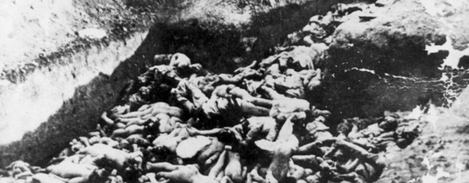 Bilden visar många döda, nakna kroppar.