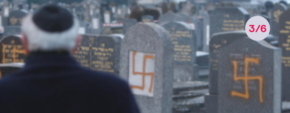 Bilden visar en man framför gravstenar med hakkors.