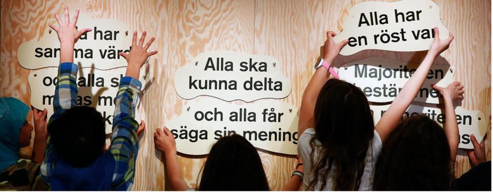 Barn fäster lappar med demokratiska budskap på en vägg