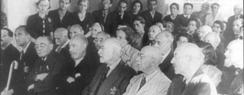 Bilden visar ett trettiotal äldre män och kvinnor sittandes. Ett tiotal yngre män och kvinnor står längs en vägg.