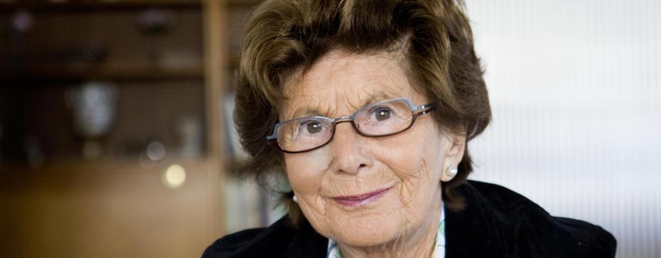 Porträtt på äldre kvinna i glasögon.