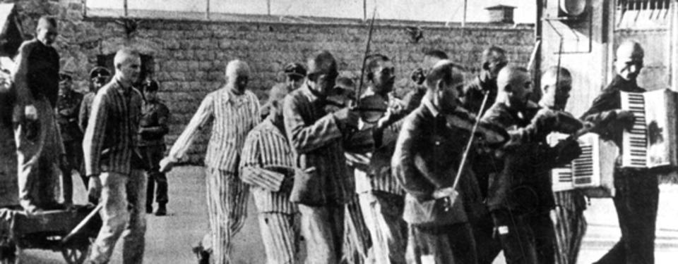Bilden visar ett tiotal män spelandes dragspel och fiol. Hög mur i bakgrunden.