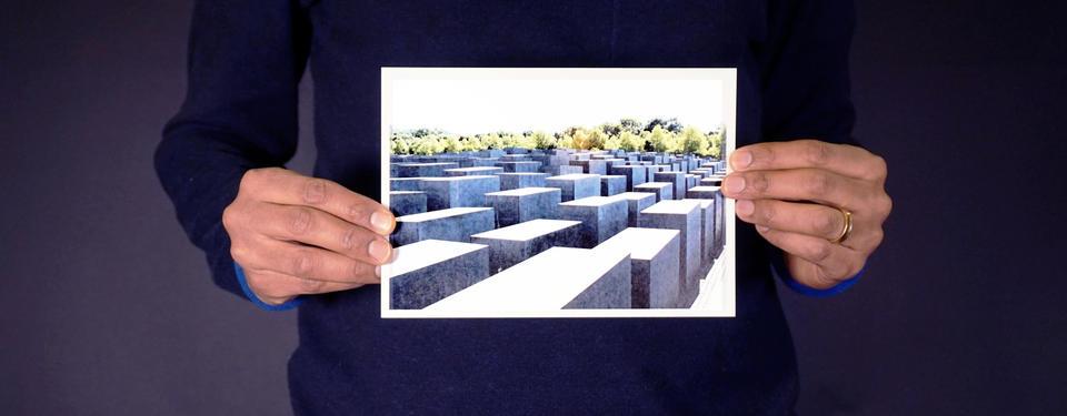 Bilden visar händer som håller i ett foto med ett minnesmonument med stora block.