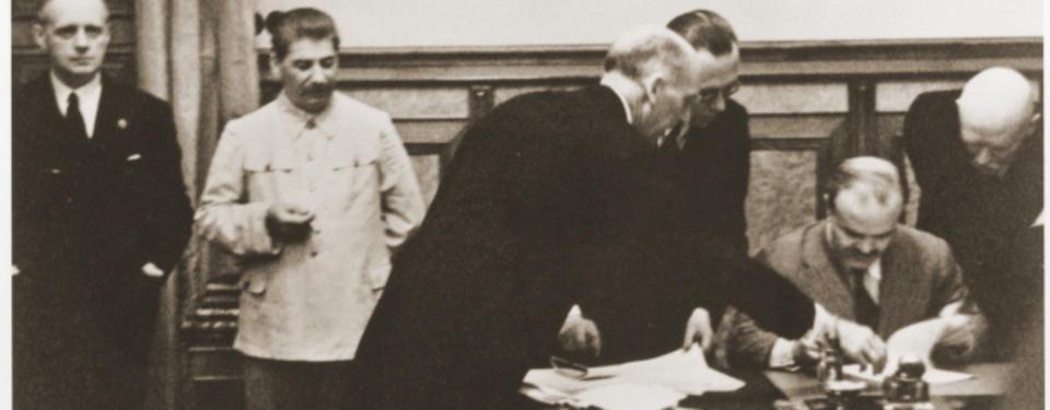 Bilden visar tre män som böjer sig fram mot bord där en man sitter med dokument framför sig.