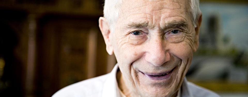 Porträtt på äldre, leende vithårig man.