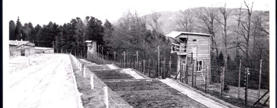 Bilden visar stängsel och vaktpostsbyggnader i trä.