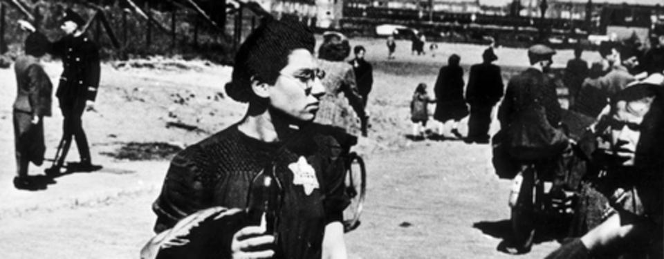 Bilden visar närbild på kvinna med judestjärna fäst på vänster sida och människor i bakgrunden.