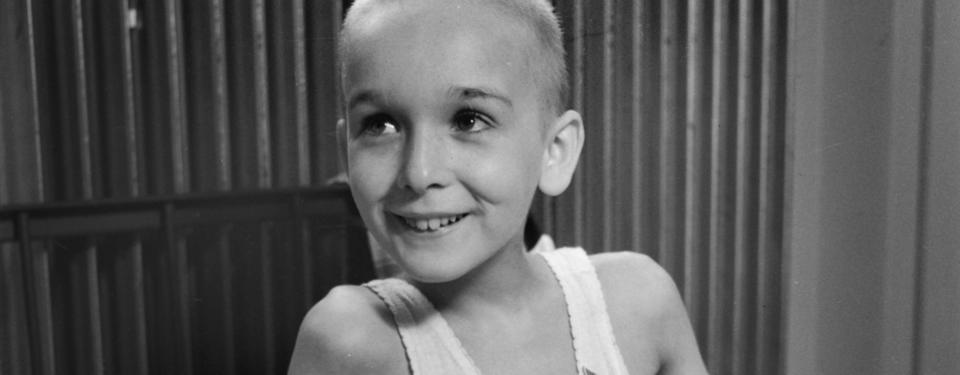 Bilden visar en ung, smal glad pojke med rakat hår.