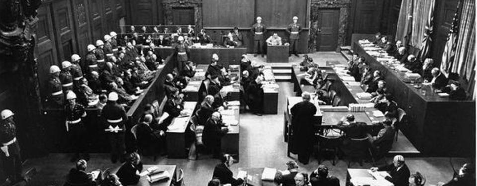 Bilden visar en stor rättssal med människor i rader.