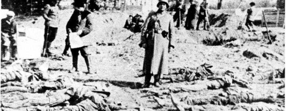 Bilden visar män i uniform bland utspridda lik som grävts upp.