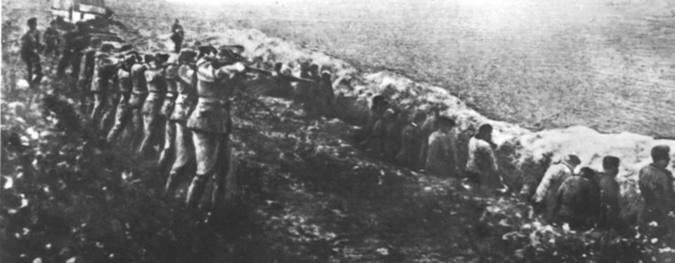Bilden visar ett femtontal soldater som siktar gevären mot uppradade civila  med ryggen åt soldaterna, ståendes ett par meter bort.