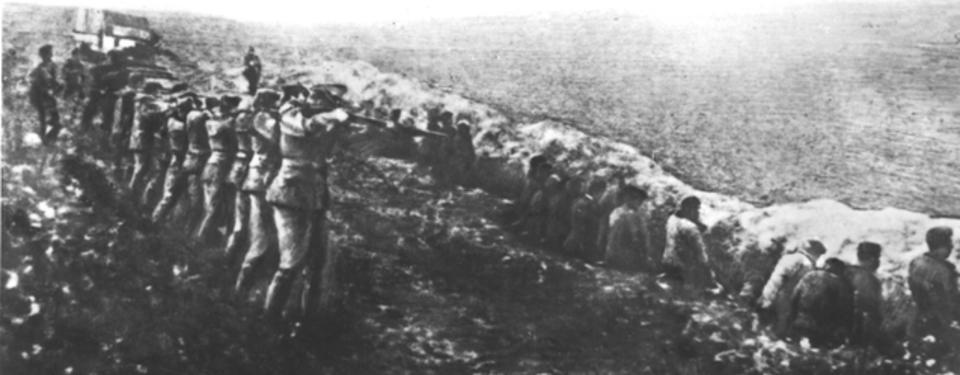 Bilden visar ett tiotal män med höjda gevär, siktandes på människor ståendes ett par meter därifrån på rad med ryggarna vända mot soldaterna.