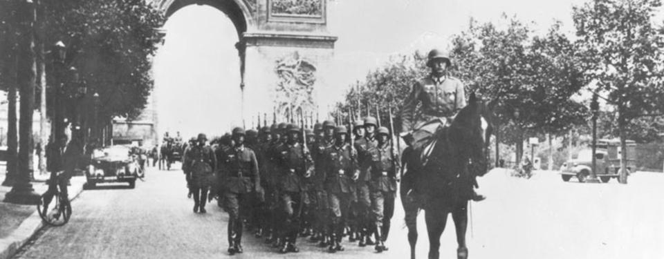 Bilden visar marscherande soldater i tre led med triumfbågen i bakgrunden.
