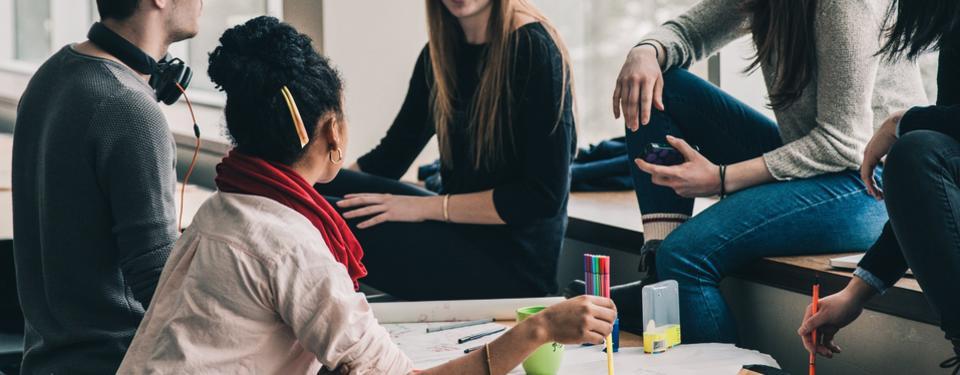 Ungdomar sitter i en grupp och samtalar med varandra
