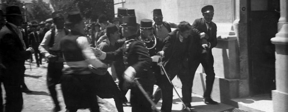 Bilden visar människor på en gata som bråkar med polis.