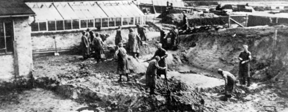 Bilden visar ett tiotal kvinnor i randiga klänningar och förkläden med spadar i händerna, övervakade av soldater.