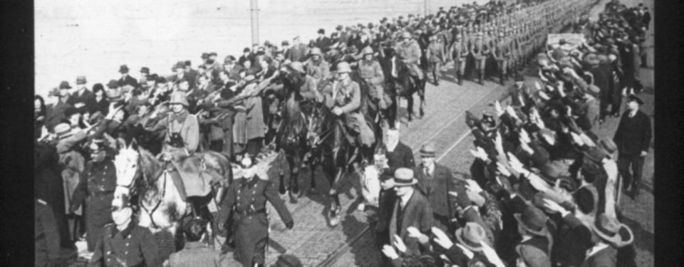 Bilden visar beridna soldater följda av gående soldater på gata, omgivna av civila hitlerhälsande människor.