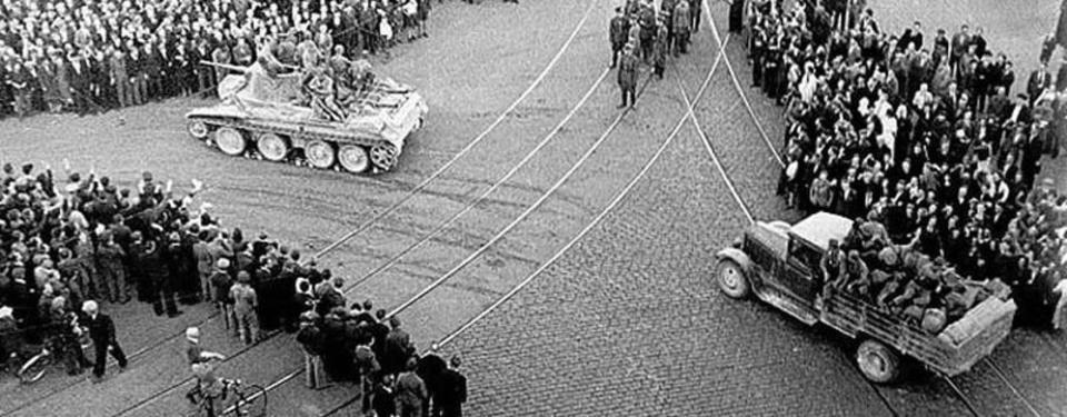 Bilden visar ett torg med människor och en stridsvagn.