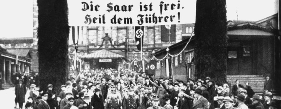 Bilden visar soldater marscherandes i stadsbild omgivna av människor. Banderoll med text Die saar ist frei. Heil dem Führer syns.