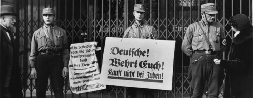 Tre soldater står vakt med plakat med budskapet köp ej av judar.