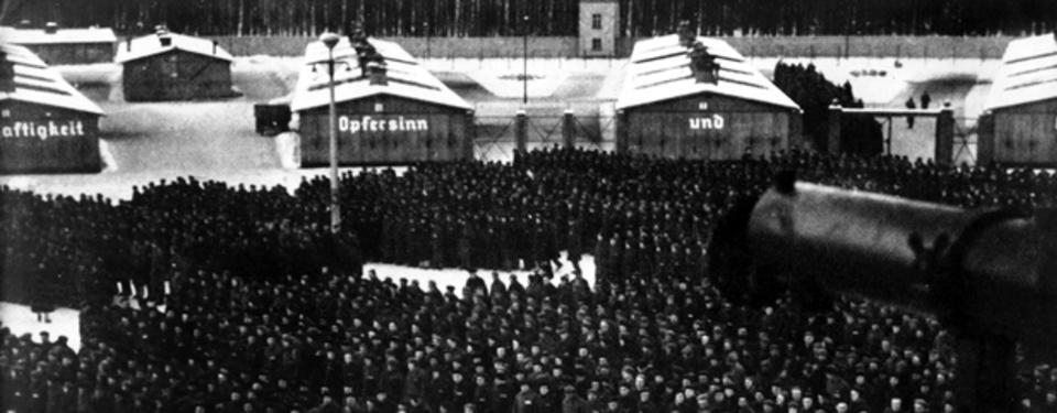 Bilden visar mängder av människor ståendes i rader på öppen plats. Barackliknande byggnader i bakgrunden.