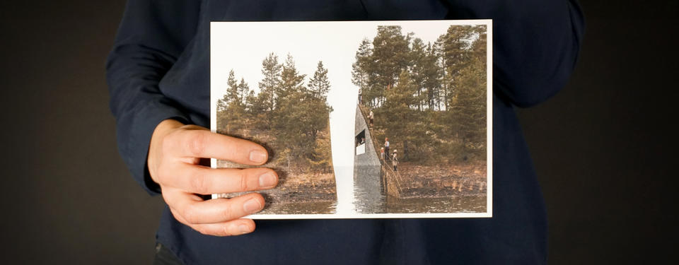 Bilden visar en hand som håller ett foto, bilden visar ett minnesmonument.