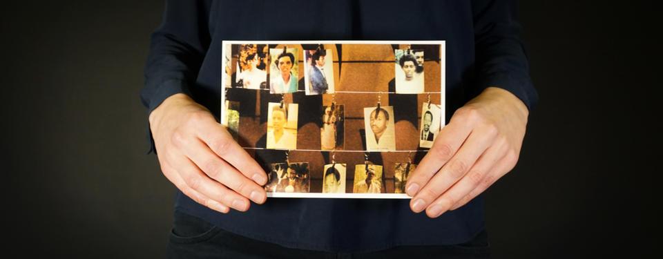 Bilden visar händer som håller i ett foto, på fotot syns fotografier av människor.