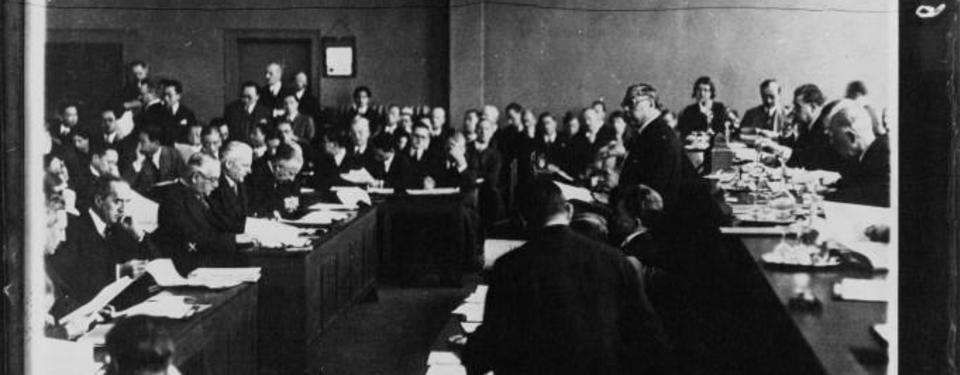 Bilden visar ett trettiotal män som sitter i ett mötesrum.