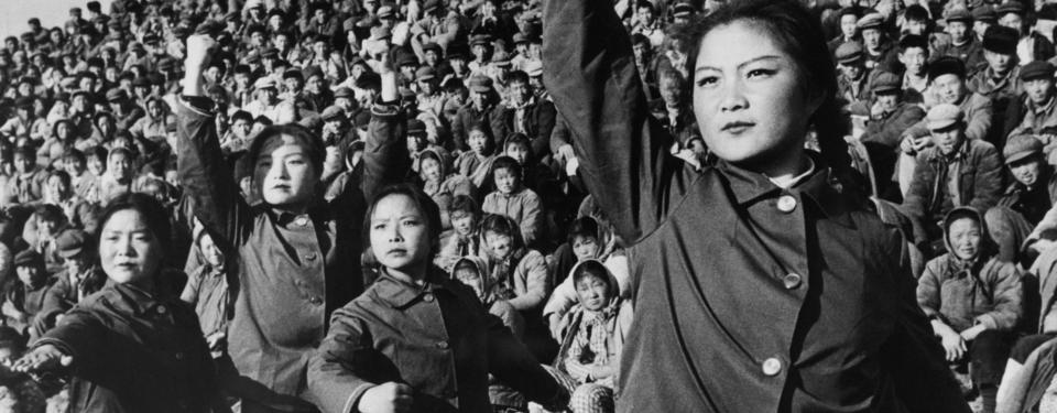 Bilden visar fyra unga allvarliga kvinnor och en stor sittande publik i bakgrunden.