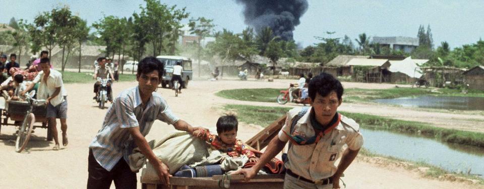 Bilden visar unga män dragandes trävagnar med tillhörigheter och barn, en mopedist på en väg, ett stort svart brandröksmoln längre bort.