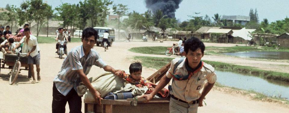 Bilden visar män gåendes på väg dragande träkärror, en mopedist och ett stort svart rökmoln i bakgrunden.