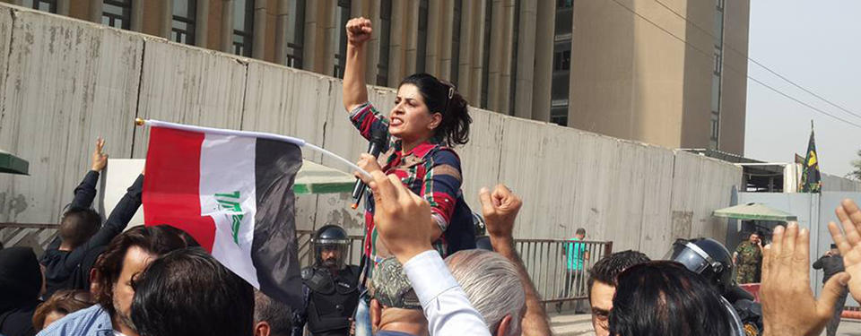 Bilden visar en kvinna som talar i en microfon med en knuten hand upp i luften.