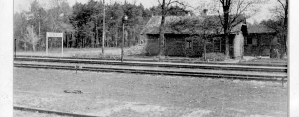 Bilden visar två järnvägsspår och två träbyggnader.