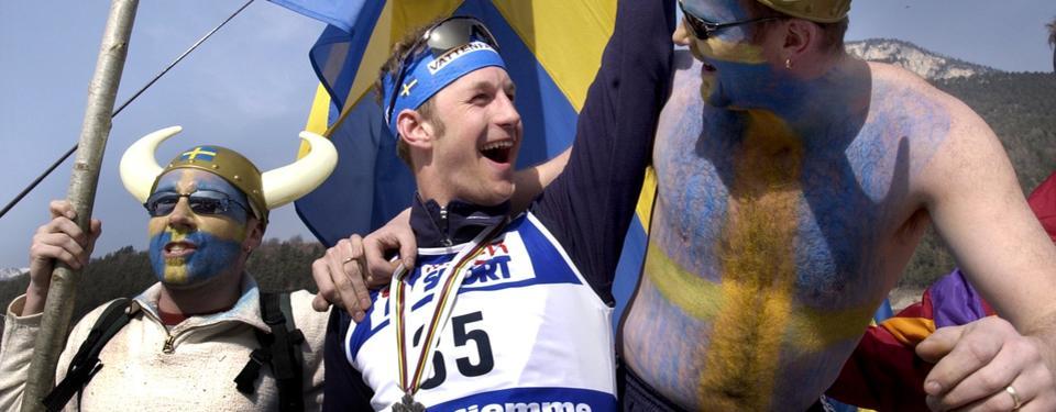 Bilden visar en mycket glad man med nummerlapp och medalj kring halsen, med en man på varsin sida om sig, målade i gult och blått.