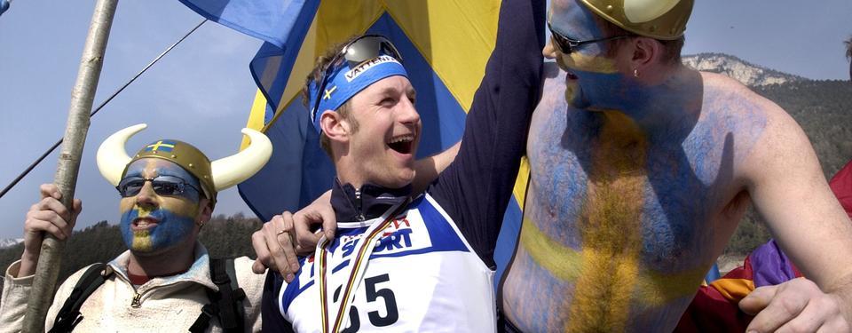 Bilden visar 3 män i blågul utsmyckning som firar.