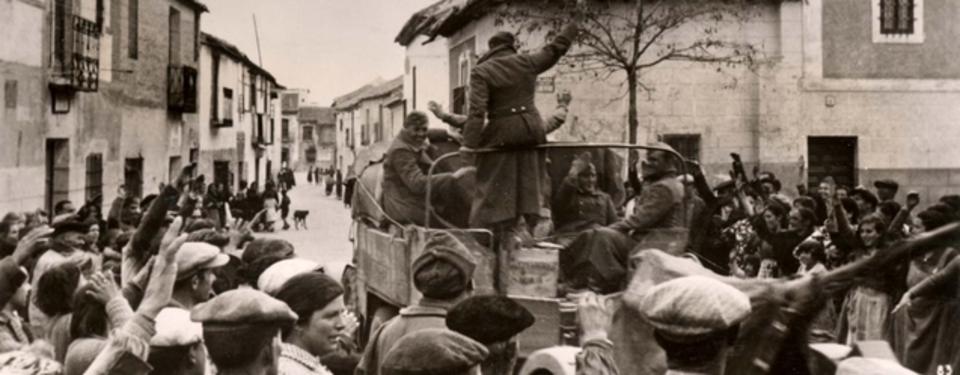 Bilden visar husomgärdad gata, soldater på fordonsflak och glada människor på båda sidor om gatan.