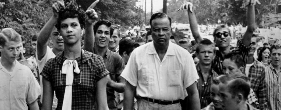 Bilden visar större mängd människor på en väg, där Dorothy Counts är en av tre personer som är främst.