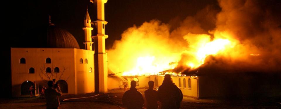 Bilden visar ett femtal personer och en fotograferande person som tittar på brandövertänkt tak till moské.