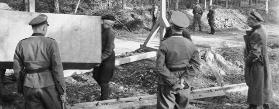 Bilden visar fem soldater som övervakar arbetet vid galgen.