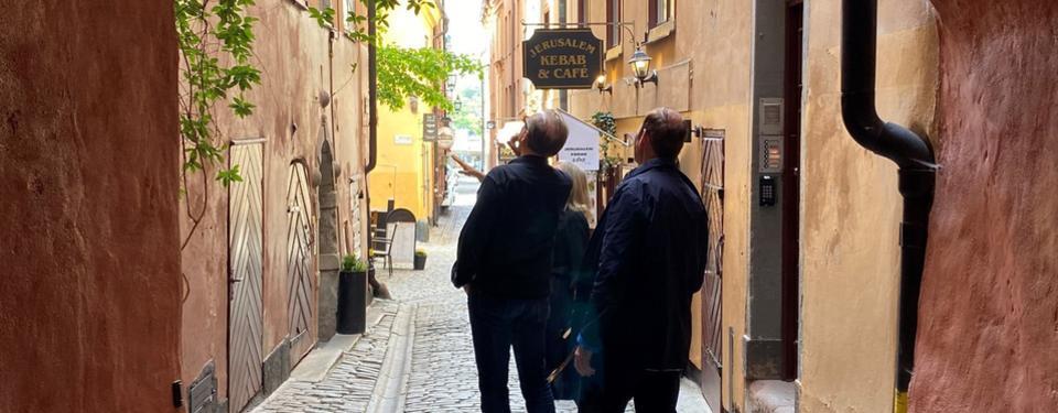 Två personer står i en gränd mellan några äldre hus och tittar upp mot en fasad.
