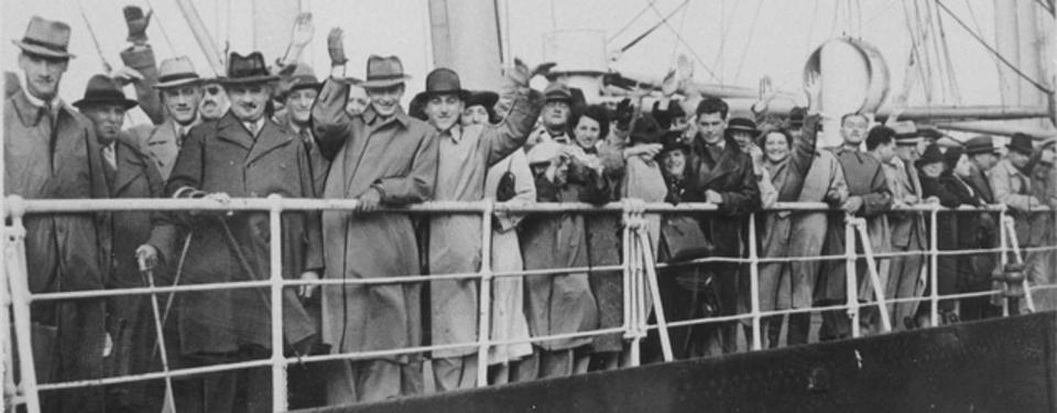Bilden visar män och kvinnor, flera vinkande, ståendes vid reling.