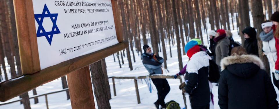 Bilden visar elever samlade i en skog med en guide.