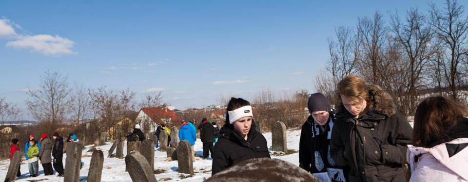 Bilden visar skolungdomar på en begravningsplats.