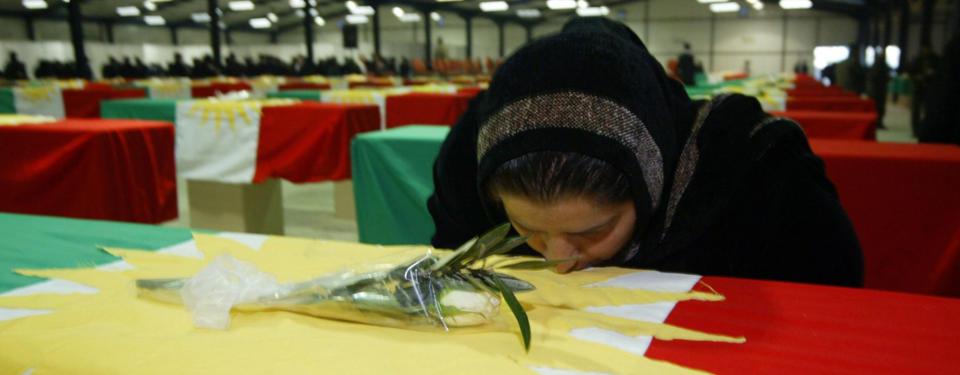 Bilden visar kvinna kyssandes flaggtäckt kista i ett stort rum med många flaggtäckta kistor.