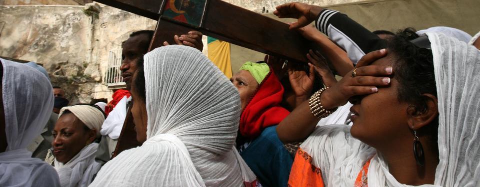 Bilden visar en man och själklädda kvinnor bärande ett träkors.