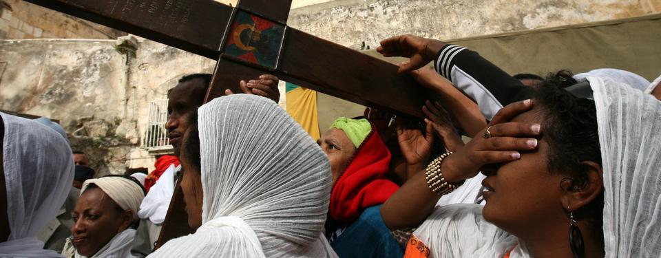 Bilden visar kvinnor som bär på ett stort kors.