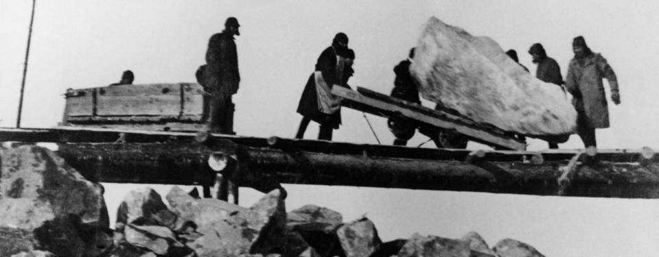 Bilden visar 5 människor som arbetar med att flytta ett stort stenblock.