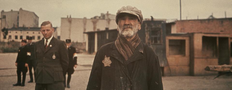 Bilden visar 2 män i ett ghetto, ena mannen bär en gul stjärna.