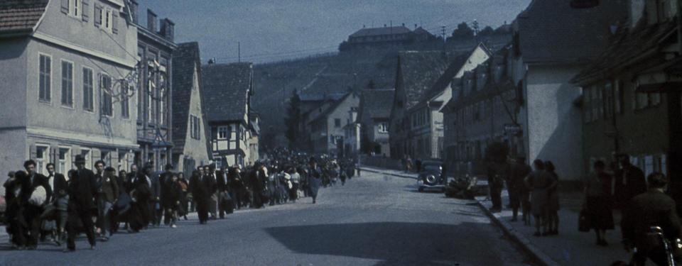 Bilden visar människor i lång kö på en gata.