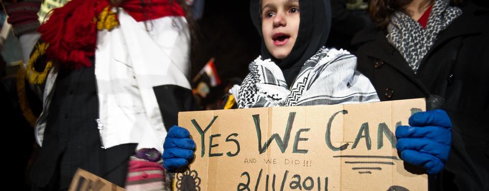 Bilden visar ett barn som håller i en skylt med texten: Yes we can